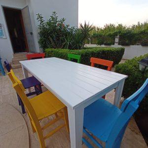 Beyaz masa ve renkli sandalyeler